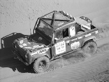 Land Rover Defender racing across dunes in Outback Challenge
